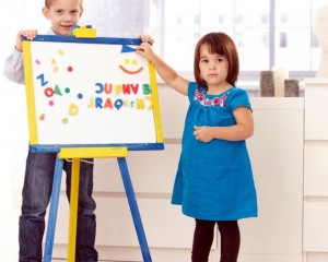 Two children playing with magnetic letter on magnetic easel